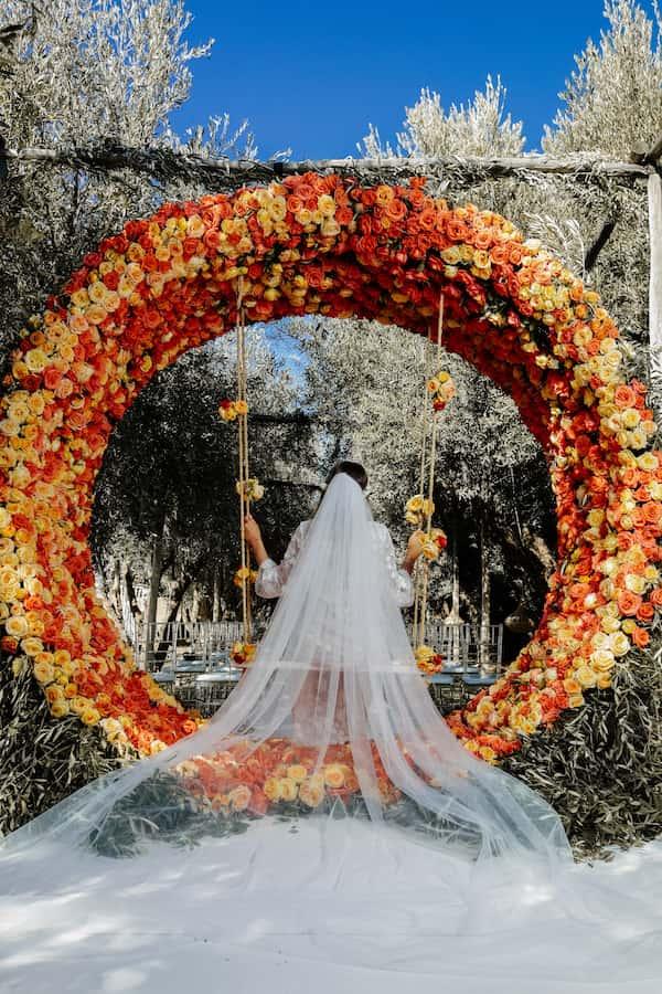 Mariée sous une arche de fleurs oranges pour un mariage à Marrakech
